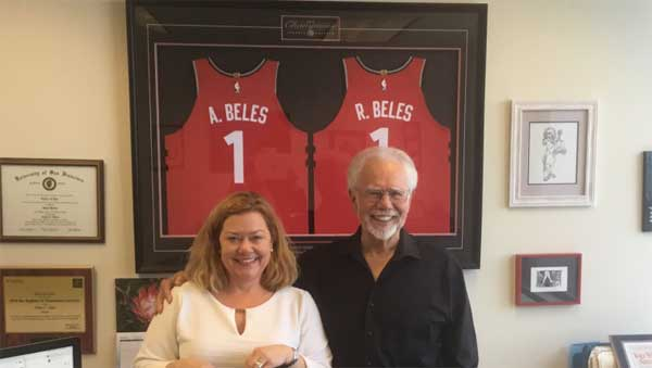 """Partners Bob and Annie Beles standing in front of 2019 NBA World Champion Toronto Raptors jerseys which were given to them in thanks for successful representation of the club president. The Raptors referred to the Beles & Beles partners as """"their dream team."""""""